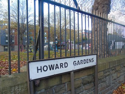 A picture of the Howard Gardens green space sign with the park in the background