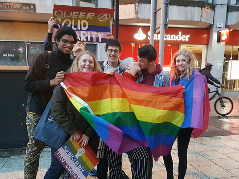 Protesters sharing the rainbow flag