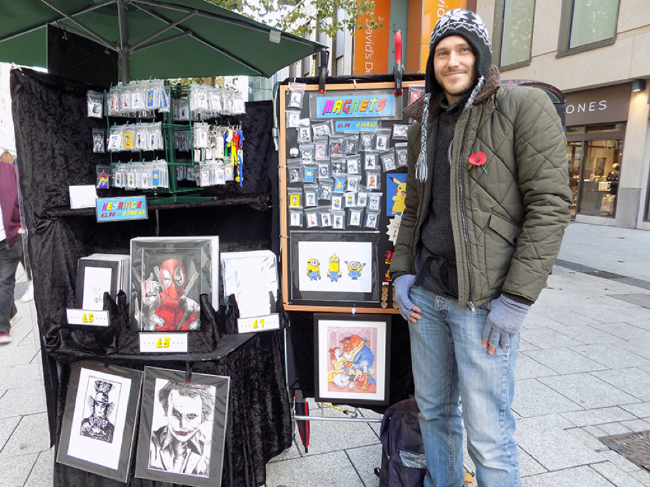 Artist Tudley James smiles wide while showcasing his art in the city centre