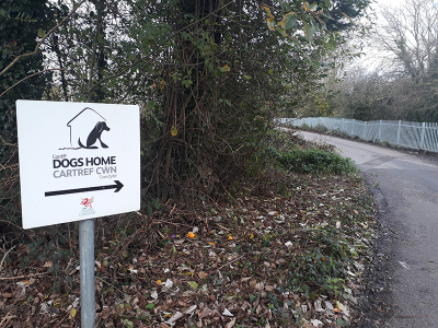 A sign for a dogs home is signalling the way to find it down a road