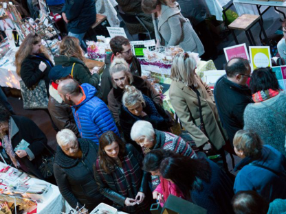 a busy crowd looking at stalls