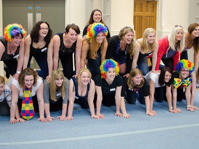 girls in colourful wigs are a human pyramid