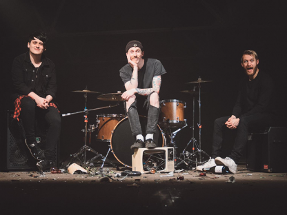 Three men are sat on a stage