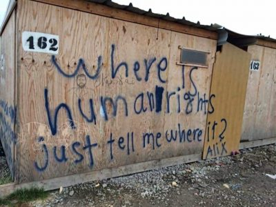 A shelter in a Calais refugee camp showing the words: where is humanity just tell me where?