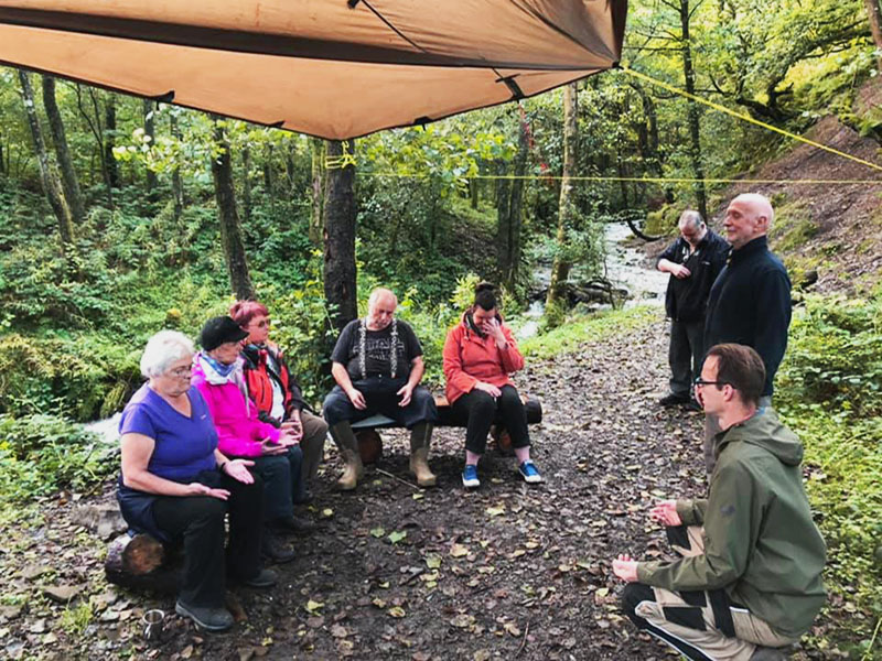 A group of people attending woodland therapy wellbeing sessions in the woods