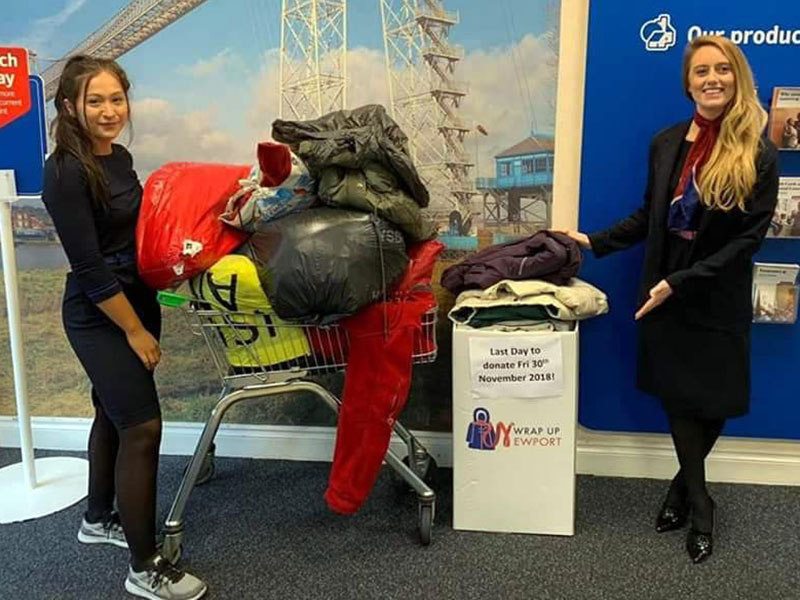 two women pose with a trolly filled with donated coats for Wrap Up Newport
