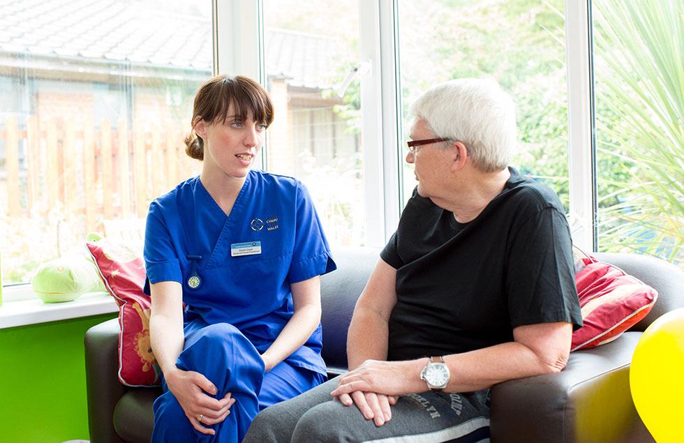nurse talking to patient on sofa