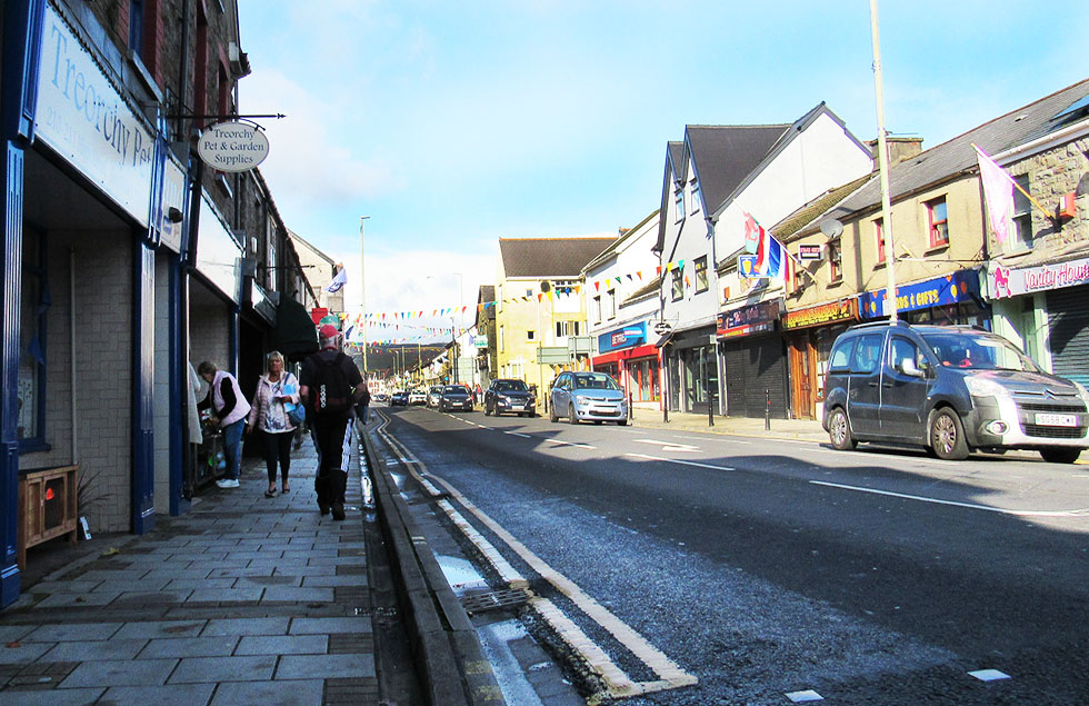 Treorchy high Street on a Saturday, showing shoppers and shop fronts, and flags and bunting