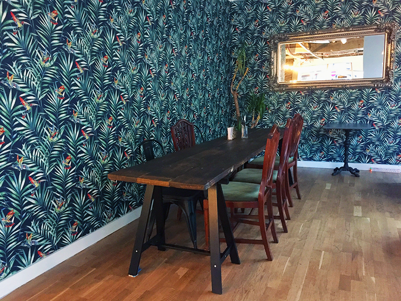 long wooden table with chairs in room with green wallpaper and mirror