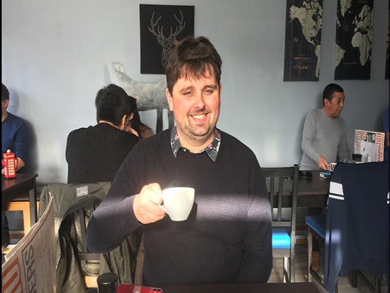 Jack Mac drinking coffee in a local cafe with a grin