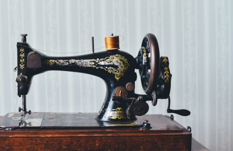 black and gold sewing machine on wooden table
