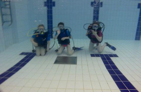three people diving in deep end of swimming pool