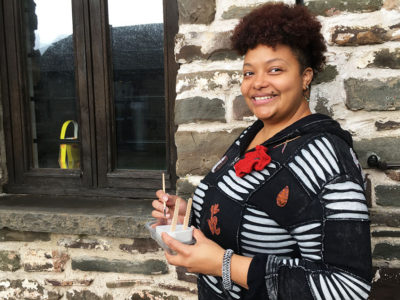 Princes Trust winner Natasha Graves stands outside her art workshop holding one of her concrete moulds for painting