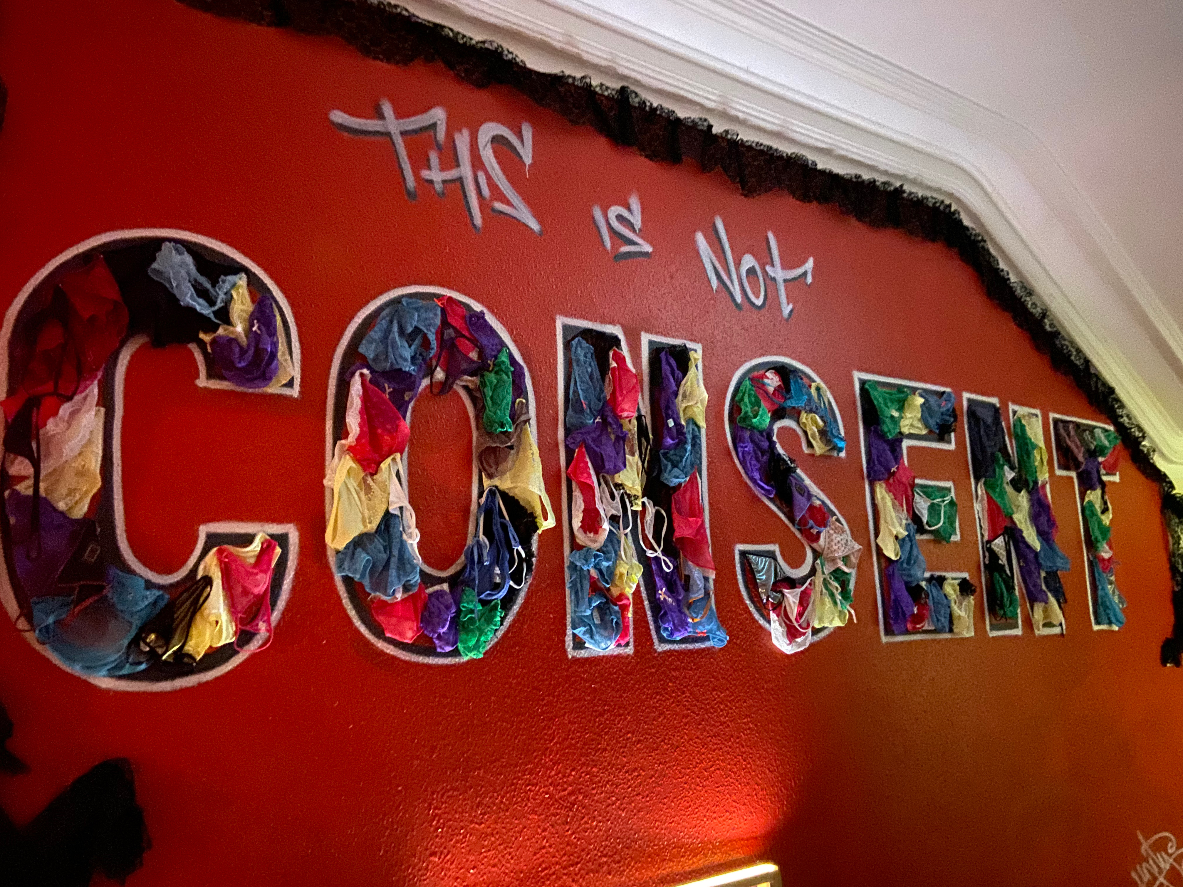 """Women's underwear is pinned on the wall to fill in the word consent, in the phrase """"this is not consent"""""""