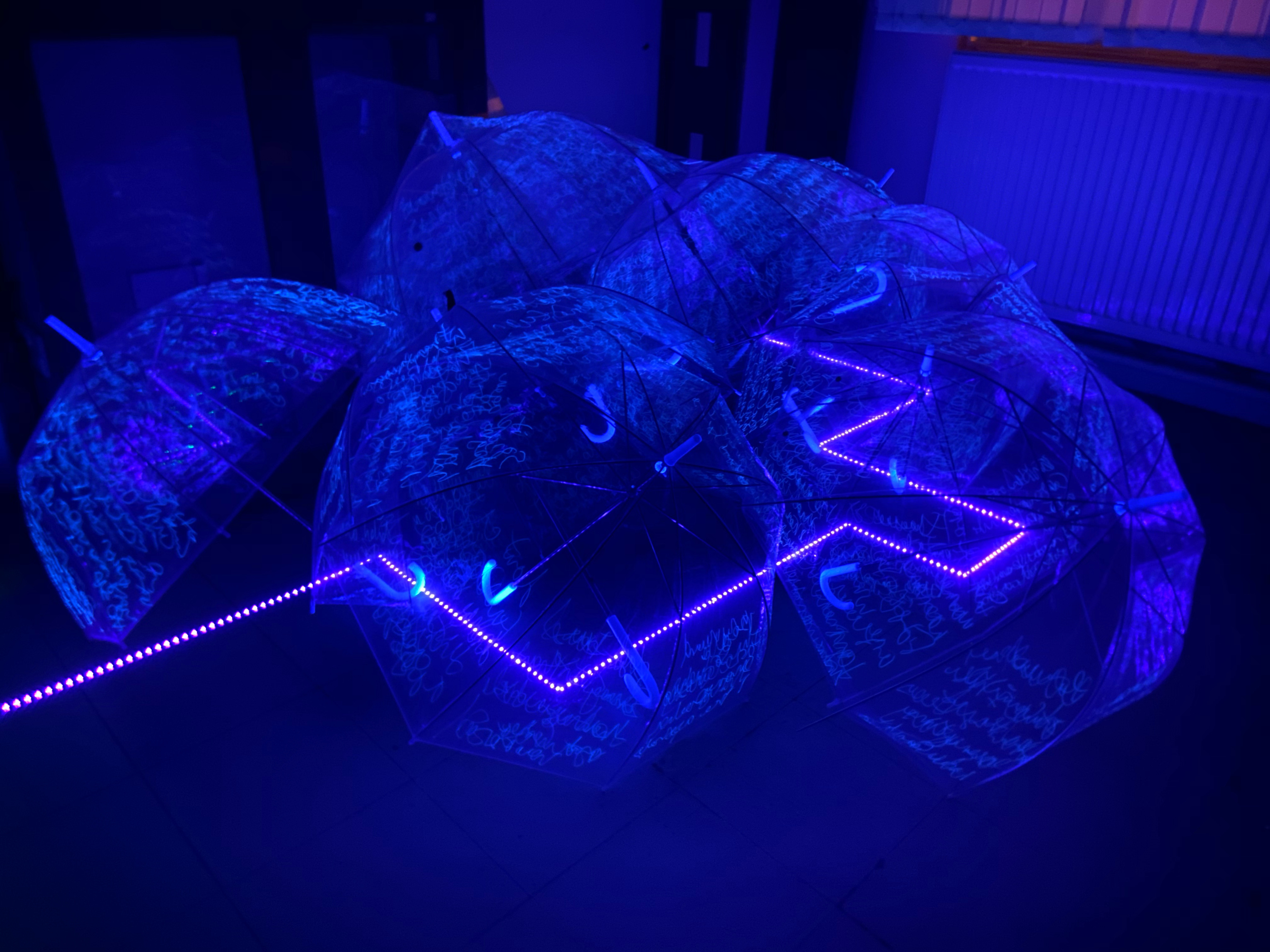 A strip of neon blue lights runs along the floor, covered by transparent plastic umbrellas with neon scrawls on them