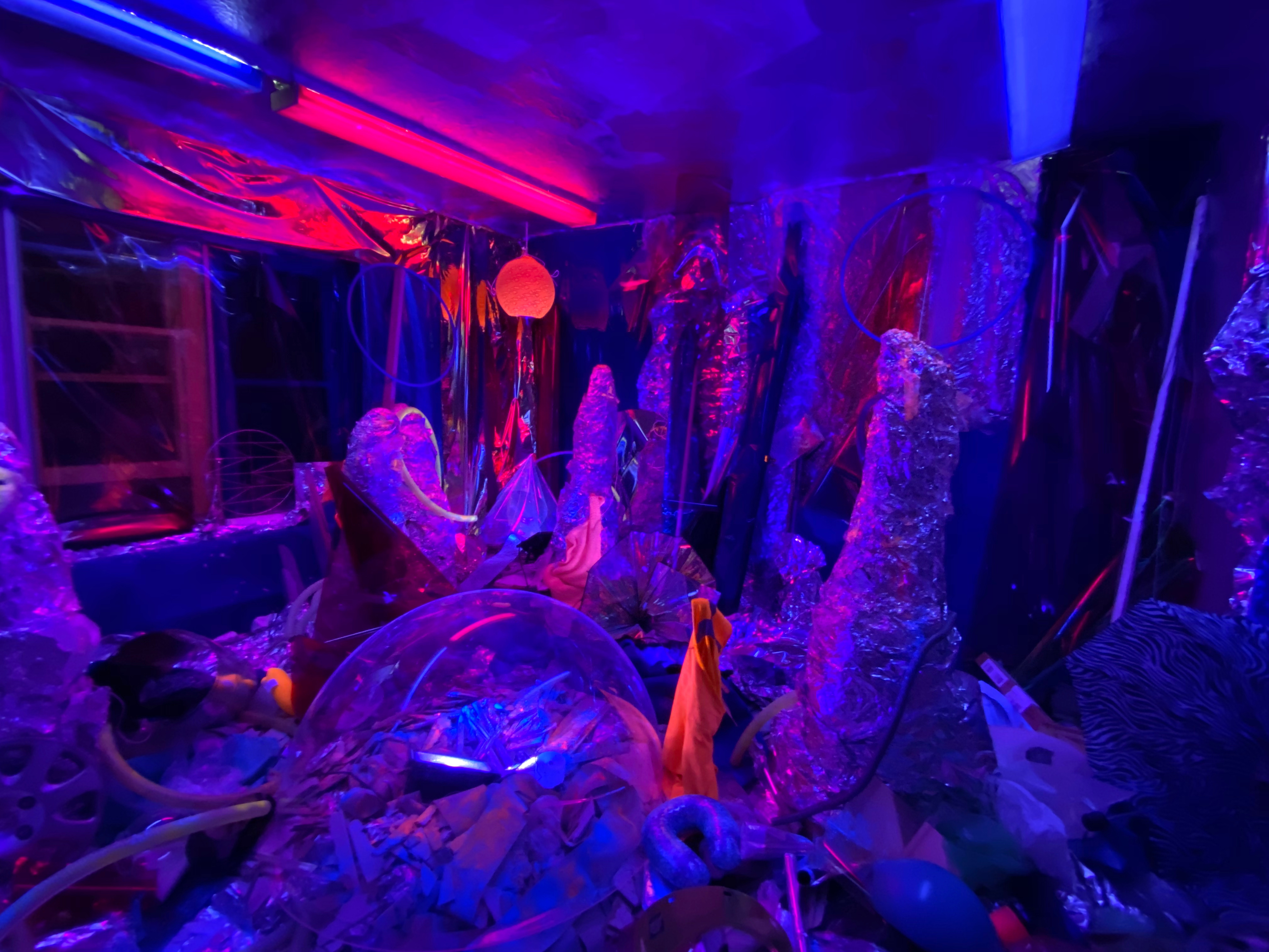 Tinfoil and clear orbs fill the room in a space-esque layout, illuminated by blue and red lights