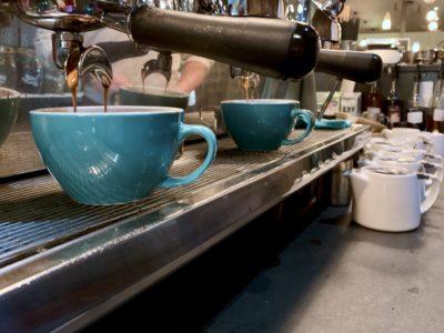 Row of blue coffee cups under espresso machine