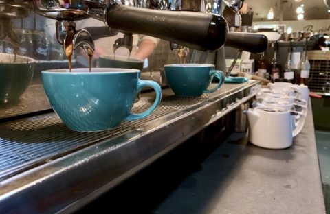 Row of blue coffee cups under espresso machine