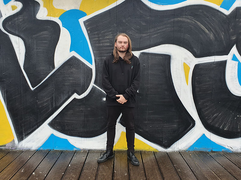 A photo of Morgan Richards of Sappenin' Podcast standing against a colourful graffiti wall in Cardiff.