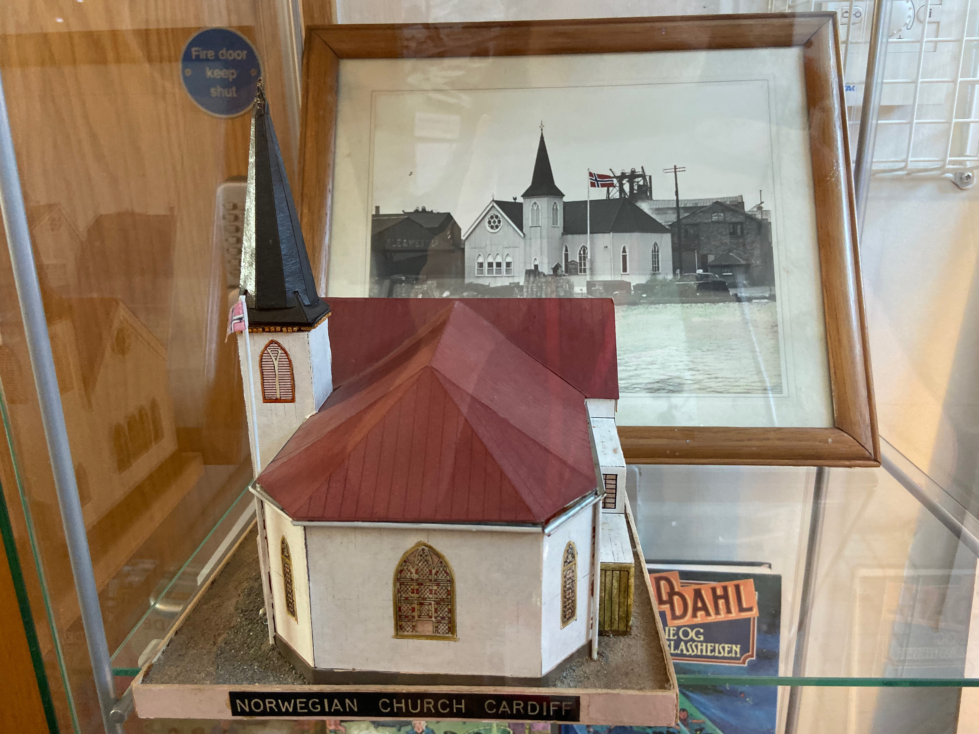 A small scale model of the Norwegian Church sits in front of an old picture of the building, inside a glass case
