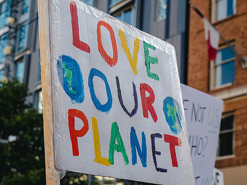 A colourful protest banner that reads 'Love Our Planet'.
