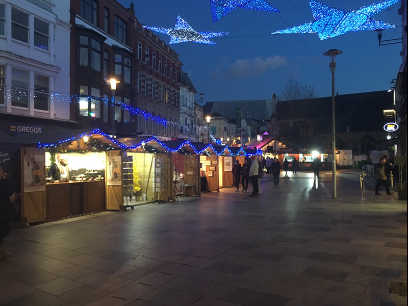 The Christmas lights over Cardiff market and people looking at the stalls.