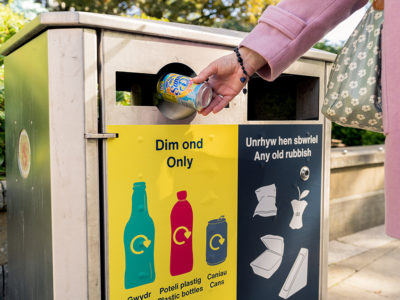 someone putting a plastic bottle in a yellow recycling bin