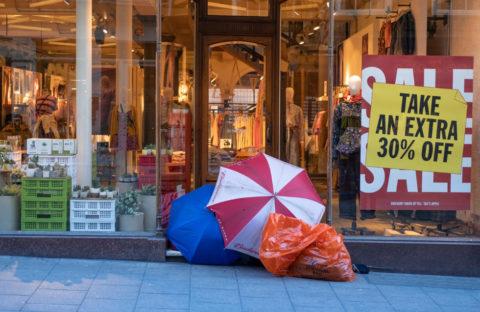 Homeless man sat outside of shop