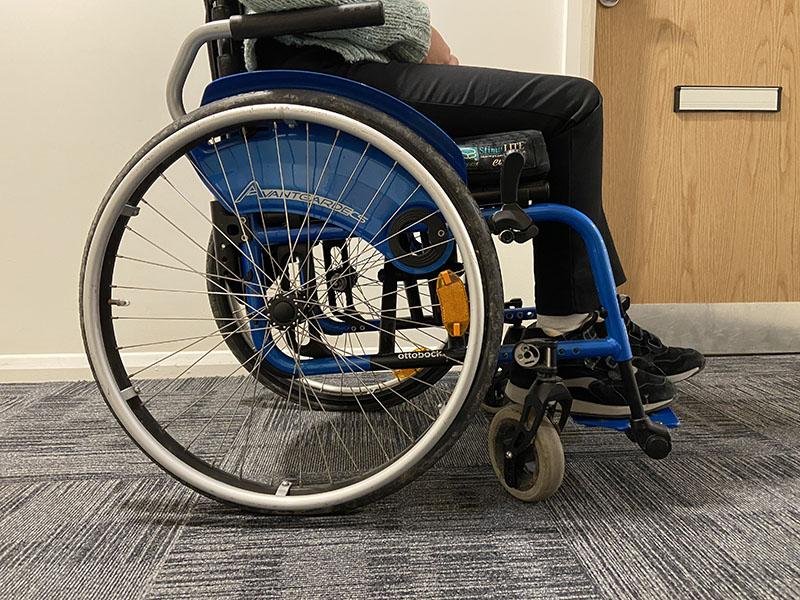 Person sitting on a blue wheelchair