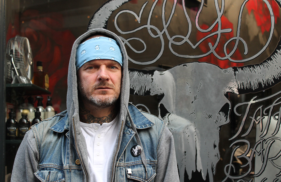 Matthew Pritchard standing outside his tattoo and barber shop, Sleep When You're Dead.