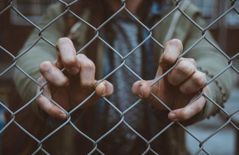 Prisoner behind a fence