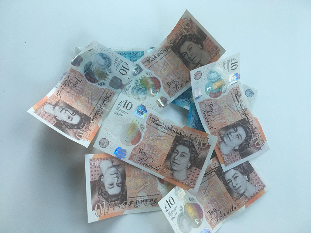 A pile of money on a table. Does the living wage dress the issue of poverty?