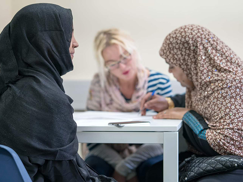 A photo of two asylum seekers in a classroom in Cardiff learning English