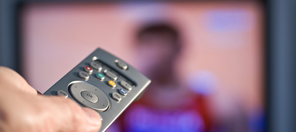 A remote control being used in front of a tv