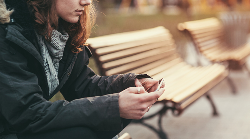 Teenage girl feeling depressed, using a smartphone