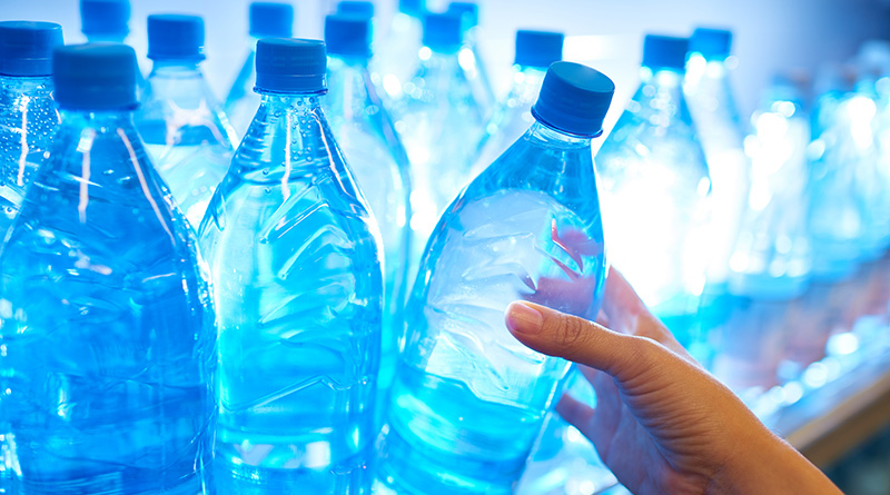 Human hand taking mineral water from shelf in supermarket