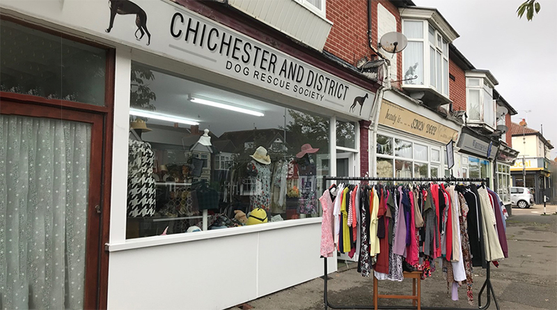 A high-street charity shop with clothes hangling on a rail outside